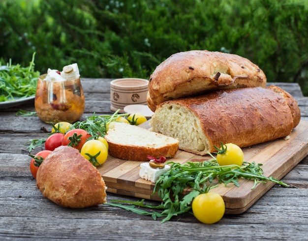 Хлеб. желтый помидор с рукколой. сыр фета с оливками и вялеными помидорами. пикник, ужин на свежем воздухе