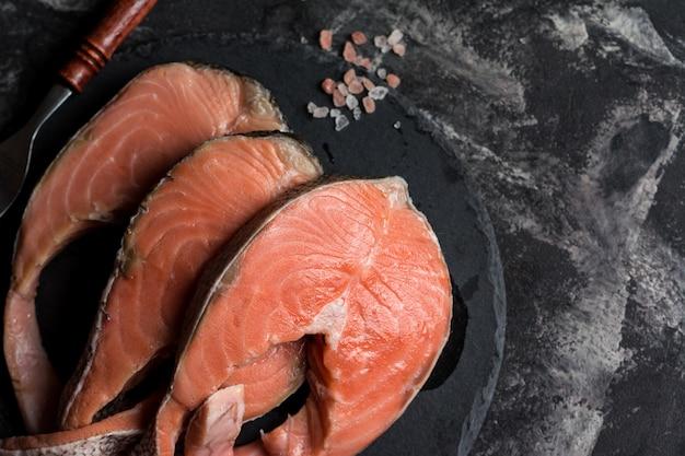 Сырой лосось, помидоры и соль на мраморном столе.