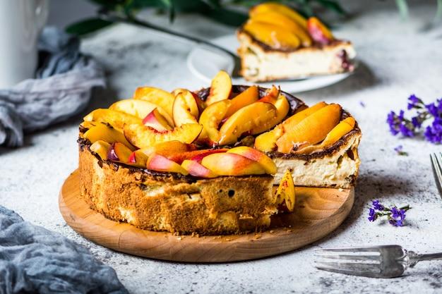 桃とニューヨークチーズケーキ。マスカルポーネチーズケーキ。健康食品。果物のデザート。夏のケーキ。食べ物の静物。ケーキ。