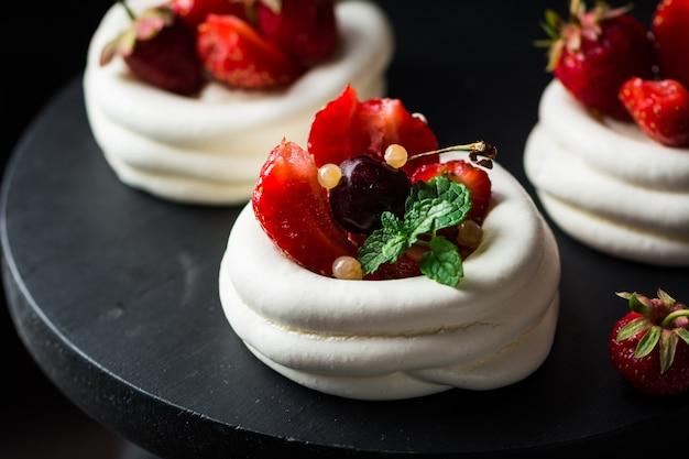 皿の上の新鮮な果実とメレンゲのデザートパブロワケーキ。夏のデザート。フレンチケーキ。お菓子。クラシックなデザート。イチゴのデザート。
