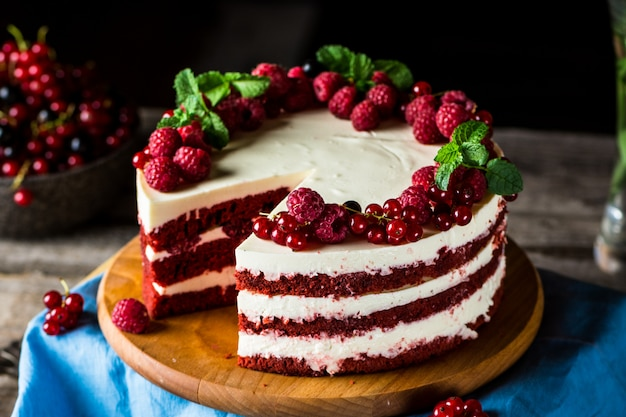 木板に赤いベルベットのケーキ。ケーキのスライス。ラズベリーケーキ。