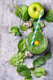 Зеленый коктейль с яблоком и листьями на бетоне