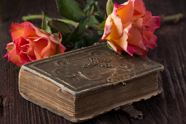 Оранжевые розы со старой книгой