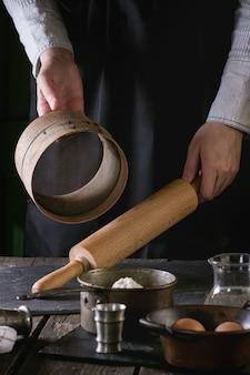 木製の麺棒とふるいの女性の手