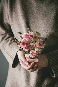 女性の手にピンクのバラ