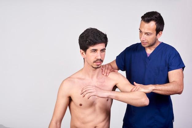 医者は診療所で彼の患者の腕を調べる