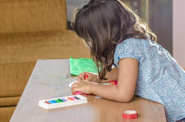 Симпатичная маленькая девочка с карандашом на фоне домашнего интерьера