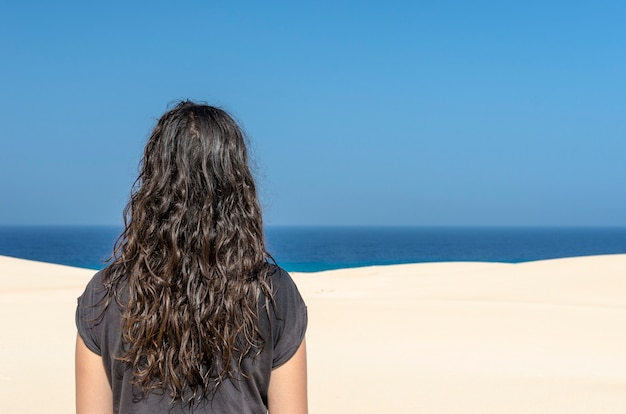 フェルテベントゥラ島の白い砂丘から海を見てブルネットの女性。