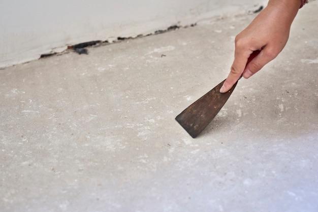 スクレーパーを持っている人は、積層木材を設置するために床から欠陥を取り除きます。部屋の中の床の修理