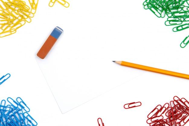 Карандаш, ластик, скрепки лежат под разными углами листа на белом фоне. изображение героя и копирование пространства.