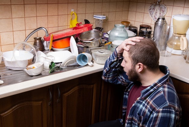 あごひげを生やした若い男が床に座っていて、洗う台所の流しに横になっている汚れた皿の量にショックを受けています。