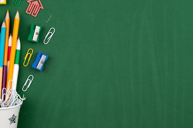 白いバケツに文房具鉛筆ペーパークリップペン消しゴム。緑の教育委員会の背景のある静物。コピースペースフラットレイアウト平面図概念教育