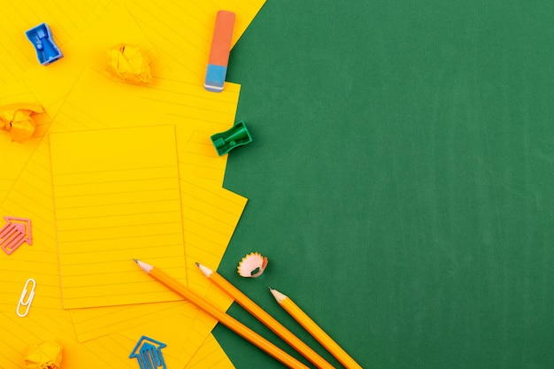 学校の文房具とオレンジ色の紙のシートが緑の教育委員会の上にあり、テキスト用のフレームを形成しています。鉛筆としわくちゃのページの近く。コピースペースフラットレイアウト平面図概念教育