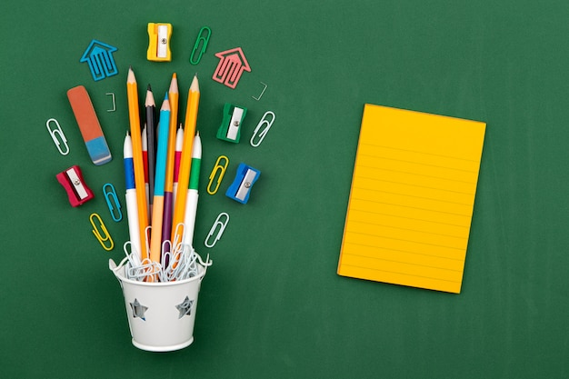 Канцелярские товары карандаши, скрепки, ластик в белом ведре. натюрморт на зеленом фоне школьного совета. копировать пространство плоская планировка вид сверху концепция образования