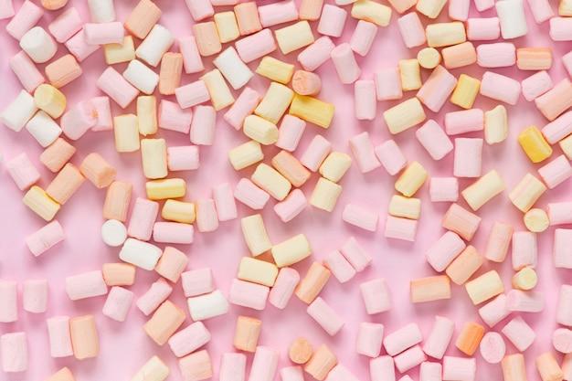 白黒ピンクの背景にマルチカラーマシュマロのトップビュー