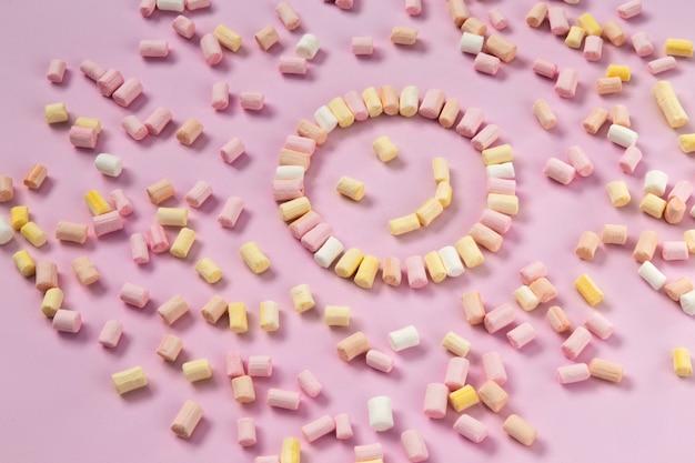 一色のピンクの背景にスマイリーや太陽の形をしたマルチカラーマシュマロの平面図