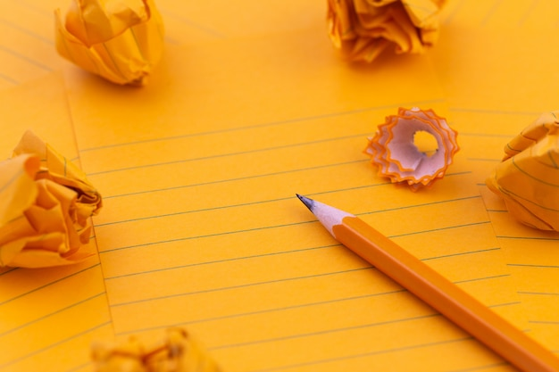コンセプトオレンジ色の紙、鉛筆、文房具、テキスト用のスペース。