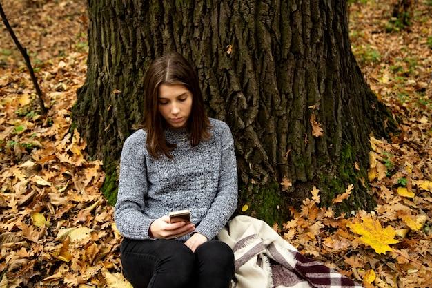 携帯電話で大きな木の近くの秋の森に座っている灰色のジャケットの美しい少女