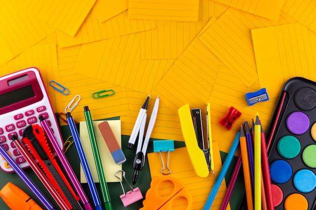 学校事務用品オレンジ色の紙の上の文房具