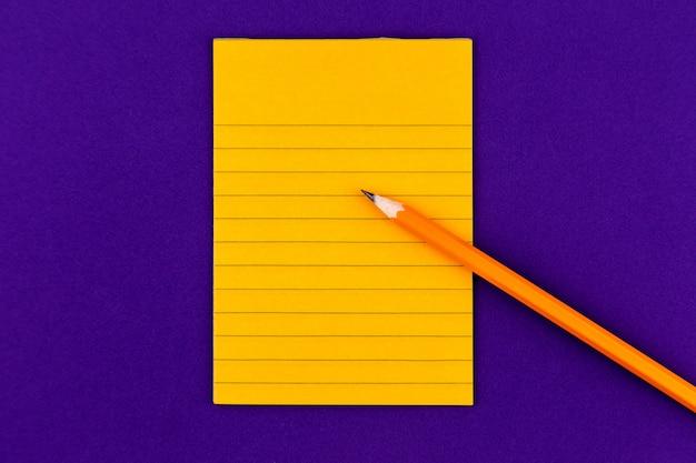 コンセプトオレンジ紙、鉛筆、文房具、あなたのテキストのための空のスペース