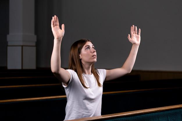 Христианская девушка сидит с поднятыми руками и лицом и смиренно молится в церкви