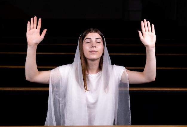 Молодая скромная девушка с платком на голове сидит в церкви и молится.
