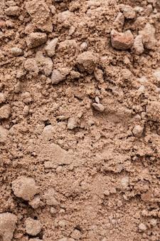 茶色の地面。自然な背景を閉じます。地面のテクスチャ、垂直