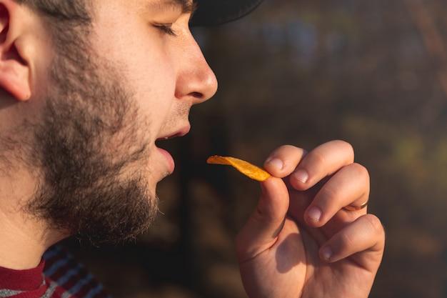 チップを食べる森のひげ男。ぼやけていると屋外の公園の画像で