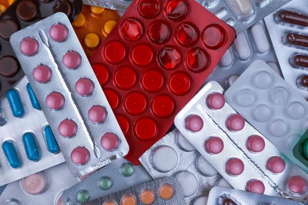 白、青、その他の色の医療薬の山。プラスチックパッケージの丸薬