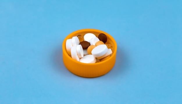 Доза разноцветных таблеток в крышке пакета таблеток. на синем фоне