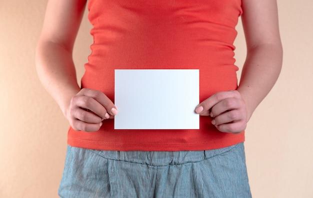 Взгляд конца-вверх живота беременной женщины в красной футболке которая держит пустой лист бумаги.