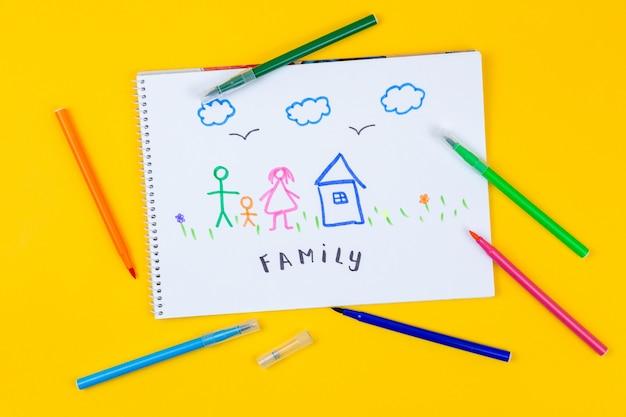 家、愛、家族、静物コンセプト。子供の絵を描く家族と一緒に紙の上に横たわるフェルトペン。セレクティブフォーカス、コピースペースの背景