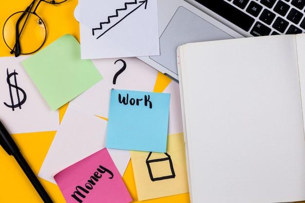 黄色の背景にノートパソコンと紙のステッカーとホームオフィスデスクのワークスペース。お金、グラフ、グラフの家フラット横たわっていた、トップビュー作業ビジネスコンセプト。コロナウイルス検疫に関する在宅勤務のコンセプト