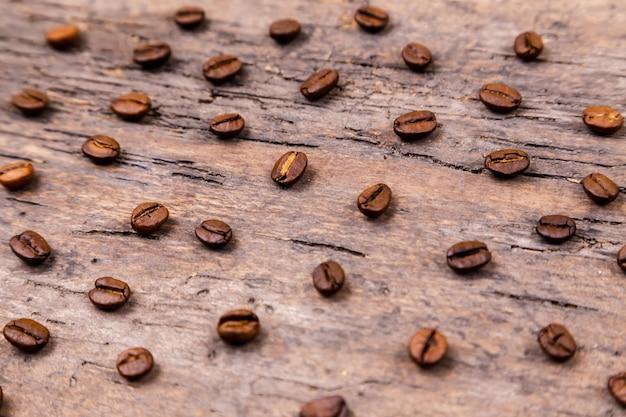 Ароматные кофейные зерна на белом деревянном столе. вид сверху. баннер