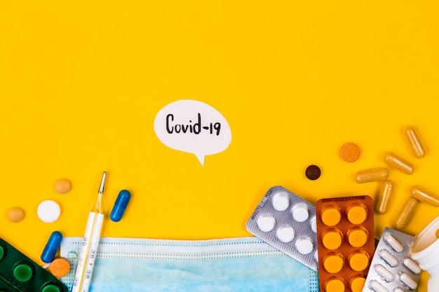 Защитная медицинская маска на желтом фоне, в окружении красочных таблетки. креативная концепция здравоохранения, гигиены, защиты от вирусов и лечения на коронавирусном карантине