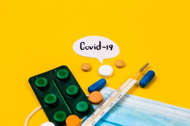 Синий хлопок медицинская защита маска на желтом фоне бумаги с таблетками. коронавирусная болезнь. концепция вируса короны. здравоохранение и медицинская концепция.