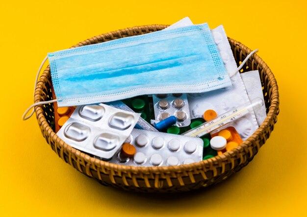 Плетеная корзина на желтом фоне. безумная маска на корзине. копировать пространство место для текста и дизайна. вид сверху. плоский макет таблетки и витамины.