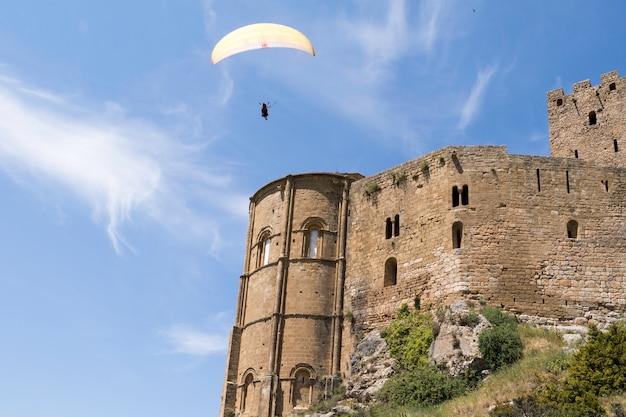 Параглайдинг в небе. парапланы пролетели над средневековым замком лоарре, уэска, испания