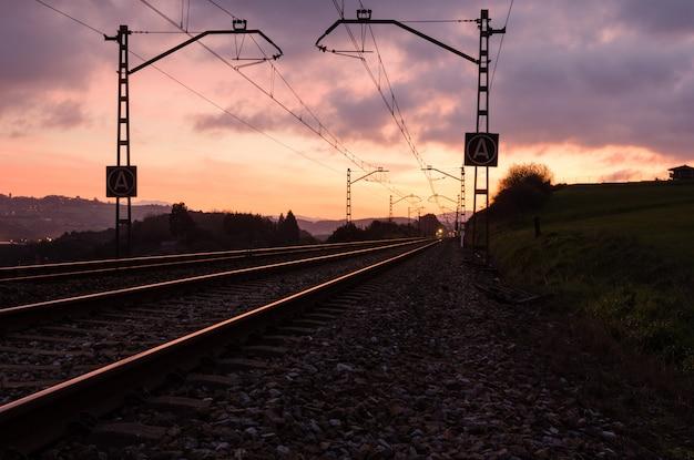 夕暮れ時の美しい空を背景の鉄道駅。鉄道のある産業景観