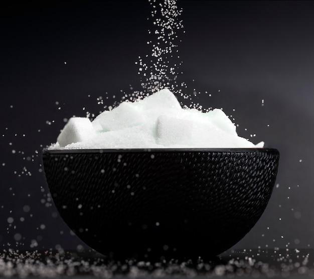 黒の背景に砂糖の立方体をボウルに落ちる白い砂糖の流れのクローズアップ