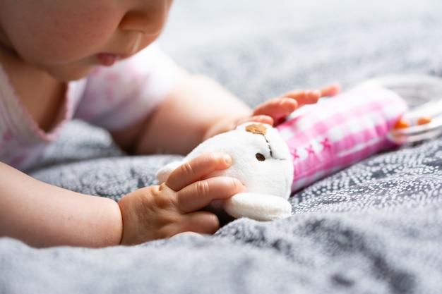 小さな子供は彼の手に彼のお気に入りのおもちゃガラガラ幸せな幼年期の赤ちゃんを保持します。