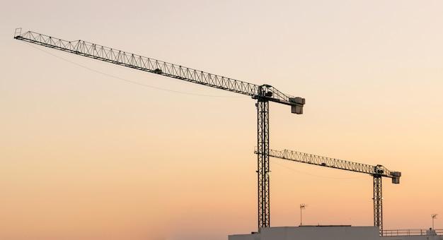 タワー建設用クレーンと夕暮れ時の美しい空を背景の建物のシルエット
