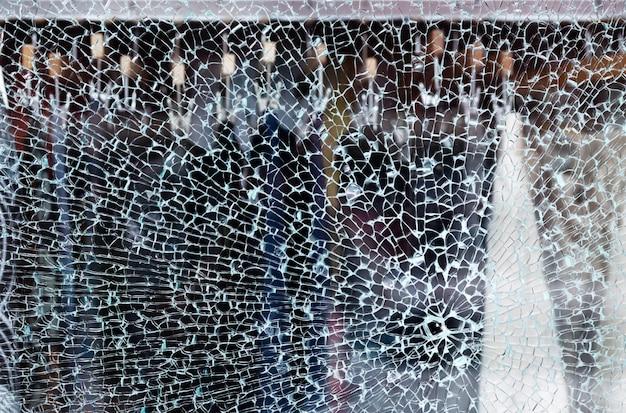 やり場のない背景を持つ衣料品店の店の窓の割れたガラス
