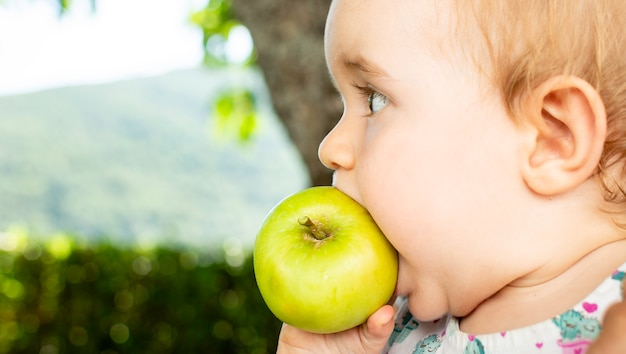 Маленький ребенок ест яблоко