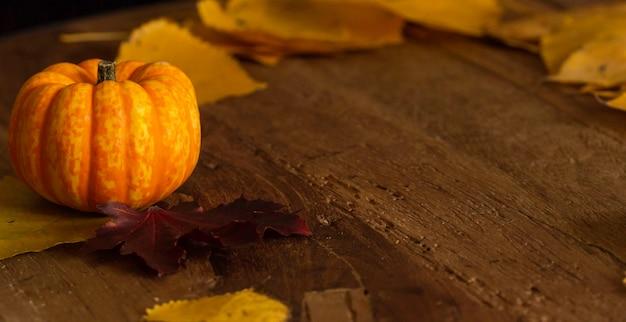オレンジ色のカボチャと木製のテーブルの落ち葉で秋の感謝祭の背景
