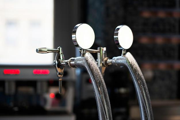 醸造所バーで光沢のあるビールタップのクローズアップ。