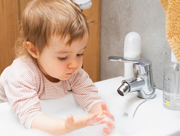 Ребенок моет руки с мылом и водой в ванной комнате