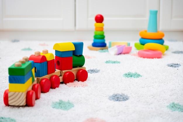 カーペットの上にカラフルな赤ちゃんのおもちゃ