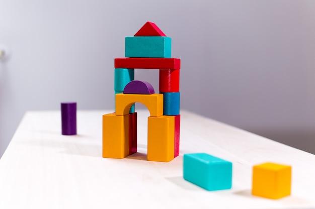 明るい色の木製のブロックのおもちゃ。塔、城、家を建てているレンガの子供たち。