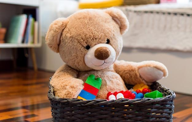 テディベアとカラフルなレンガと子供のおもちゃの背景。